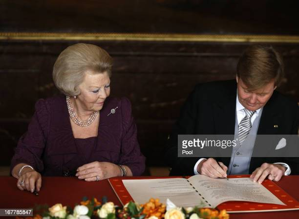 Prince WillemAlexander of the Netherlands signs his name to the Act of Abdication as his mother Queen Beatrix of the Netherlands watches during her...