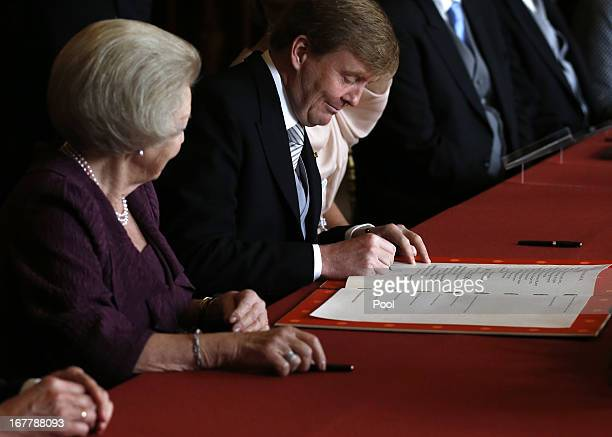 Prince WillemAlexander of the Netherlands signs the Act of Abdication during the abdication ceremony for his mother Queen Beatrix of the Netherlands...
