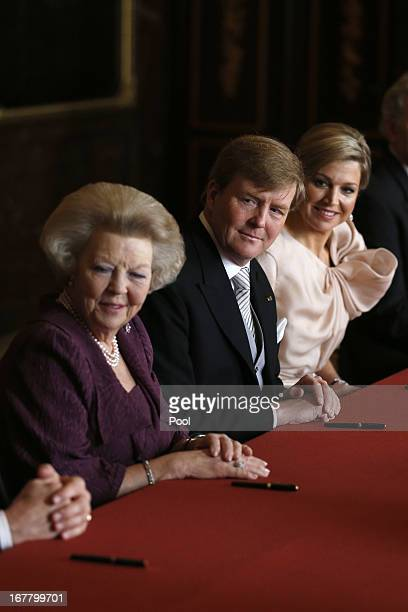Prince WillemAlexander of the Netherlands sits alongside his wife Princess Maxima of the Netherlands during the abdication ceremony of his mother...