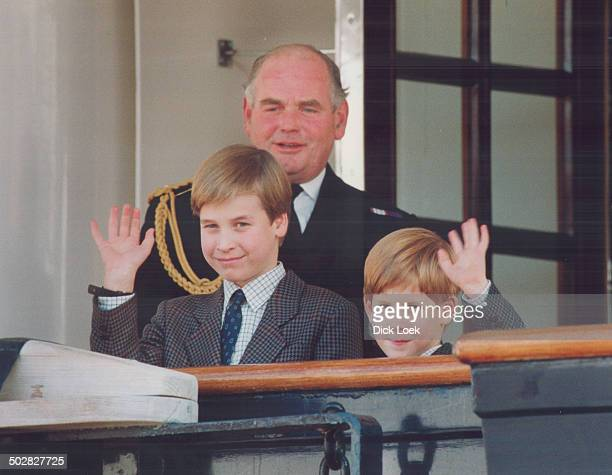 Prince William 9 and Prince Harry 7 wave after arriving at the royal yacht Britannia yesterday watched over by the vessel's captain Rear Admiral...