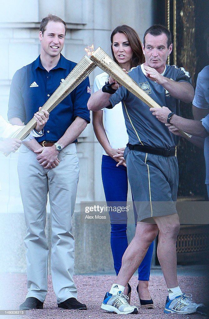 Prince William and Catherine, Duchess Of Cambridge Greets The Olympic Torch As It Arrives At Buckingham Palace on July 26, 2012 in London, England.