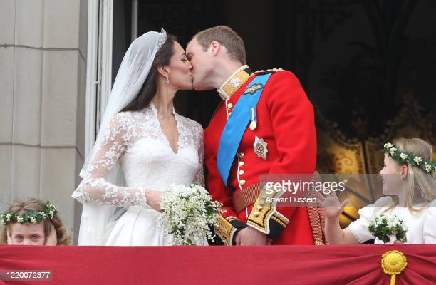 Prince William and his bride Catherine Middleton, watched by bridesmaids Grace Van Cutsem and Margarita Armstrong-Jones, kiss on the balcony of...