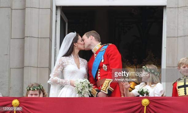Prince William and his bride Catherine Middleton watched by bridesmaids Grace Van Cutsem and Margarita ArmstrongJones kiss on the balcony of...
