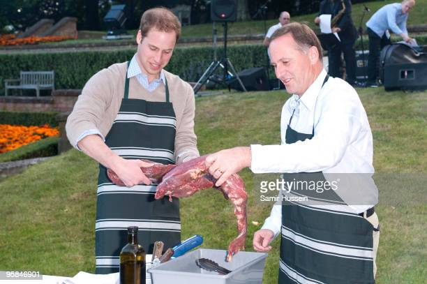 Prince William and John Key Prime Minister of New Zealand prepare meat at a barbecue at Premiere House on the second day of his visit to New Zealand...