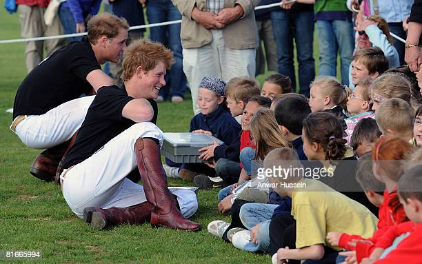 Prince William and Prince Harry chat to local children after competing in a charity polo match at the the Beaufort Polo Cub on June 22 2008 in...