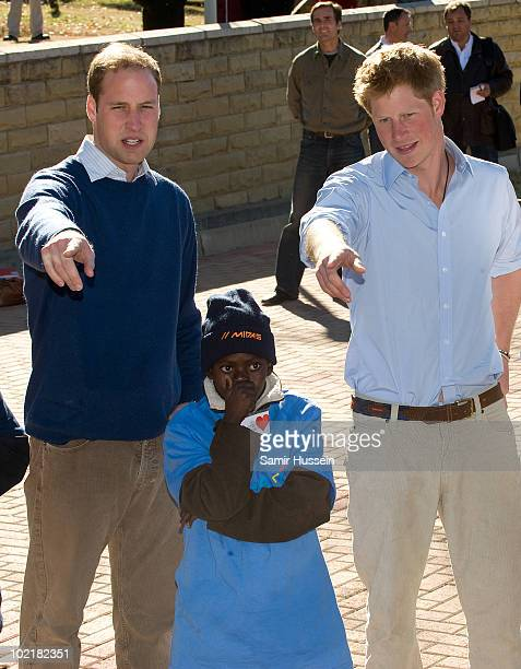 Prince William and Prince Harry meet a child at the Mamohato Network Club for children affected by HIV at King Letsie's Palace on June 17, 2010 in...