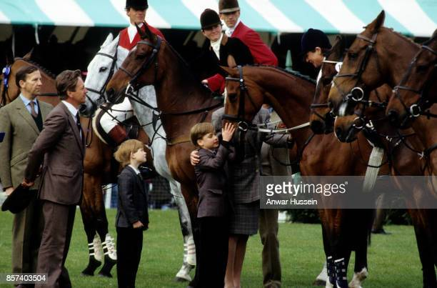 Prince William and Prince Harry pat a horse when they visit the Badminton Horse Trials on May 10 1991 in London England