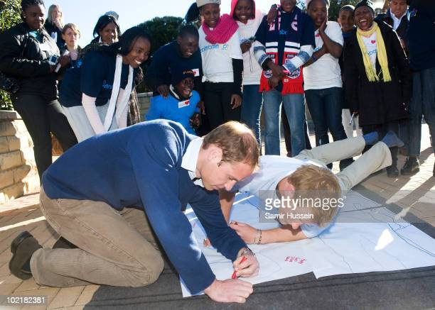 Prince William and Prince Harry take part in a game in which they have their bodies outlined and then write down their future wishes at the Mamohato...
