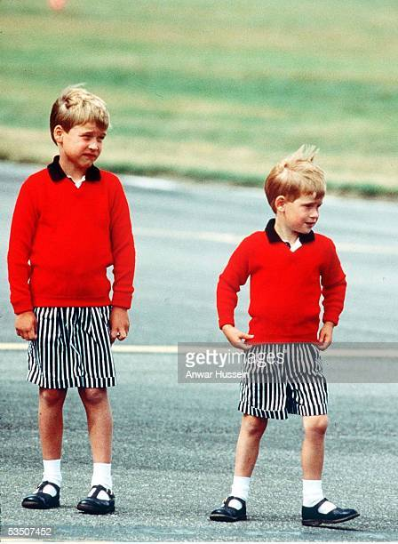 Prince William and Prince Harry wearing identical red jumpers and stripey shorts arrive at Aberdeen Airport at the start of their holidays in...