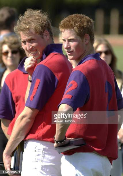 Prince William and Prince Harry wearing number 1 and number 2 polo shirts smile after playing in the St James's Place polo day charity match for the...