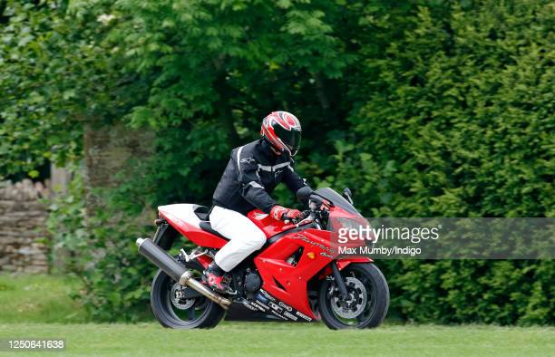 Prince William arrives riding his Triumph Daytona 600 motorbike to play in the Burberry Cup polo match at Cirencester Park Polo Club on June 17 2005...