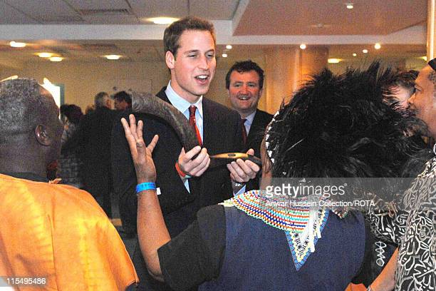 Prince William blows into a Kudu horn after watching displays by the Rhonddabase Valleys Kids charity group and the South African Group 'Amampondo'...