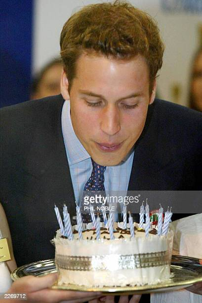 Prince William blows out the candles on a birthday cake given to him, 19 June 2003, during a visit to the Anglesey Food Fair in north Wales. The...