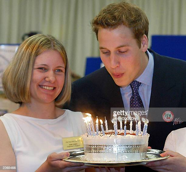 Prince William blows out the candles on a birthday cake held by an unidentified girl, 19 June 2003, during a visit to the Anglesey Food Fair in north...