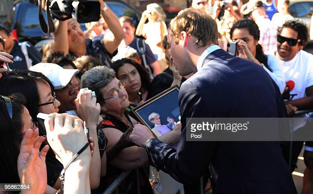 Prince William chats with a woman holding a photograph of the Prince's late mother Princess Diana as he meets with members of the local Redfern...