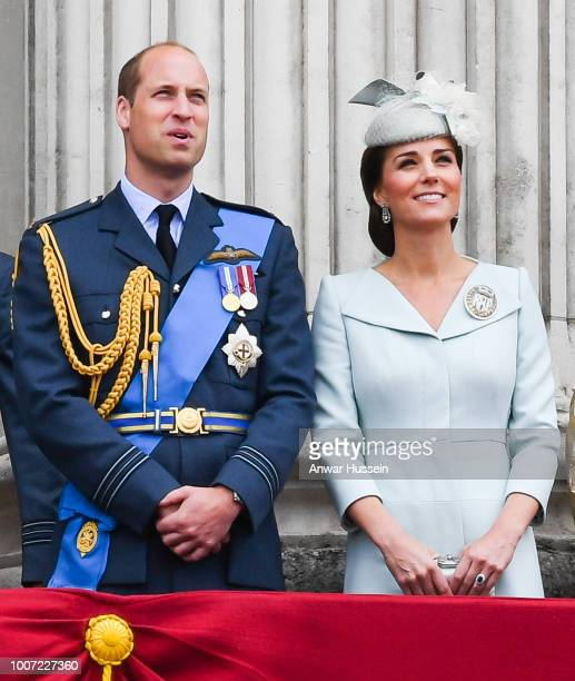Prince William Duke of Cambridge and Catherine Duchess of Cambridge stand on the balcony of Buckingham Palace to view a flypast to mark the centenary...