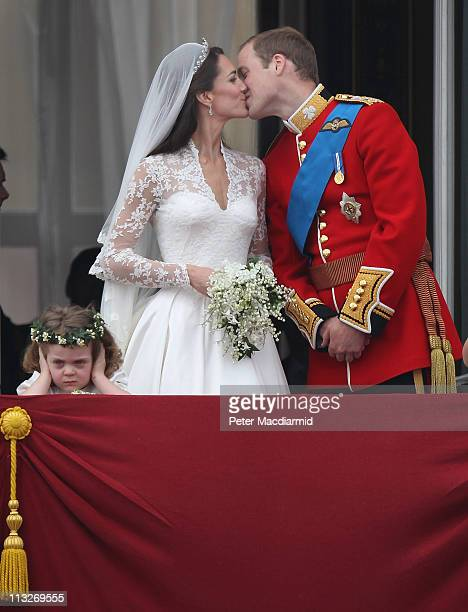 Prince William Duke of Cambridge and Catherine Duchess of Cambridge kiss as Bridesmaid Grace Van Cutsem looks at the crowd from the balcony at...