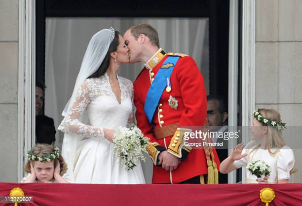 Prince William Duke of Cambridge and Catherine Duchess of Cambridge kiss next to Grace Van Cutsem and Margarita ArmstrongJones on the balcony at...