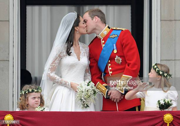 Prince William, Duke of Cambridge and Catherine, Duchess of Cambridge kiss next to Grace Van Cutsem and Margarita Armstrong-Jones on the balcony at...