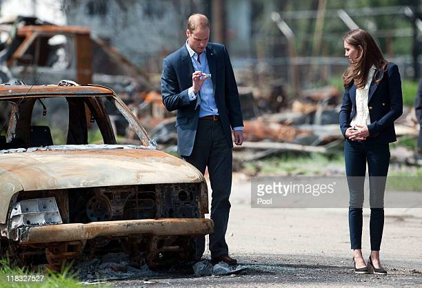 Prince William Duke of Cambridge and Catherine Duchess of Cambridge inspect a firedamaged car in a part of town devastated by a fire in May 2011 on...