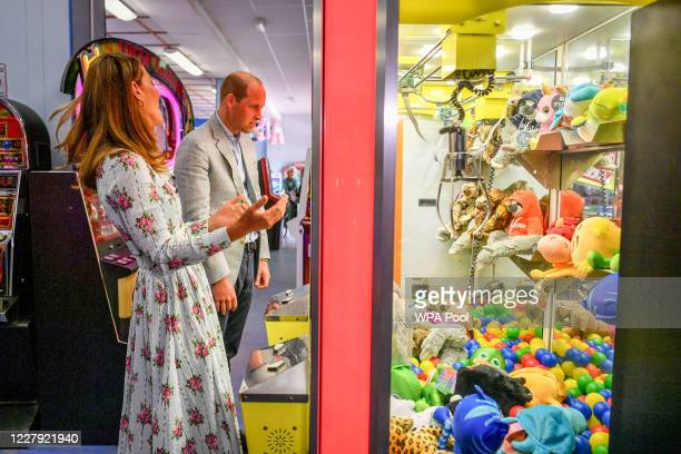 Prince William Duke of Cambridge and Catherine Duchess of Cambridge play a grab a teddy game as the Duchess turns to the Duke after picking up a blue...