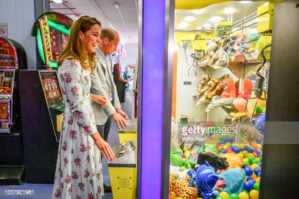 Prince William Duke of Cambridge and Catherine Duchess of Cambridge play a grab a teddy game as the Duchess laughs after picking up a blue toy and...