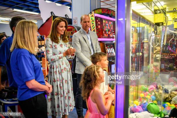 Prince William Duke of Cambridge and Catherine Duchess of Cambridge warch children play a grab a teddy game at Island Leisure Amusement Arcade where...
