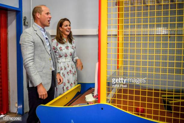 Prince William Duke of Cambridge and Catherine Duchess of Cambridge laugh after throwing balls to knock down figures on an arcade game at Island...