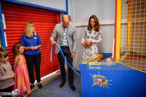 Prince William Duke of Cambridge and Catherine Duchess of Cambridge collect their winning tickets after throwing balls to knock down figures on an...