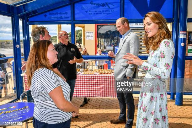 Prince William Duke of Cambridge and Catherine Duchess of Cambridge chat with business owners inside Marco's cafe during the Duke and Duchess of...