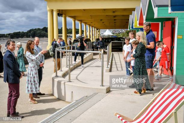 Prince William Duke of Cambridge and Catherine Duchess of Cambridge chat to the Hughes family as they visit beach huts during their visit to Barry...