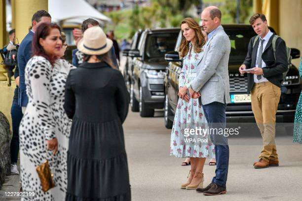 Prince William Duke of Cambridge and Catherine Duchess of Cambridge chat to people on the promenade as they visit beach huts during their visit to...