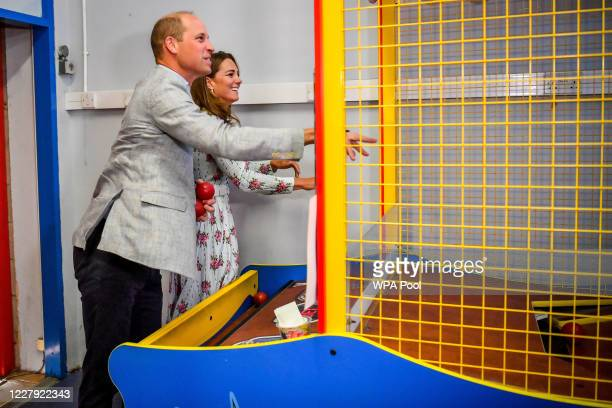 Prince William Duke of Cambridge and Catherine Duchess of Cambridge throw balls to knock down figures on an arcade game at Island Leisure Amusement...