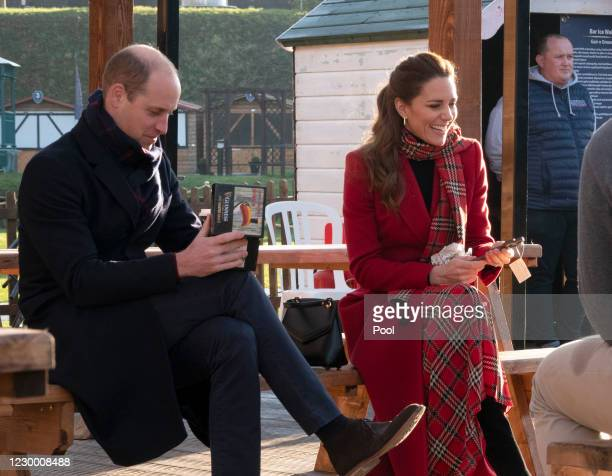 Prince William, Duke of Cambridge and Catherine, Duchess of Cambridge open their Secret Santa presents during a visit to Cardiff Castle to meet local...