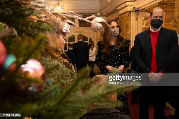 Prince William, Duke of Cambridge and Catherine, Duchess of Cambridge speak to Dom Warren, the founder of Doms Food Mission, and family as they...