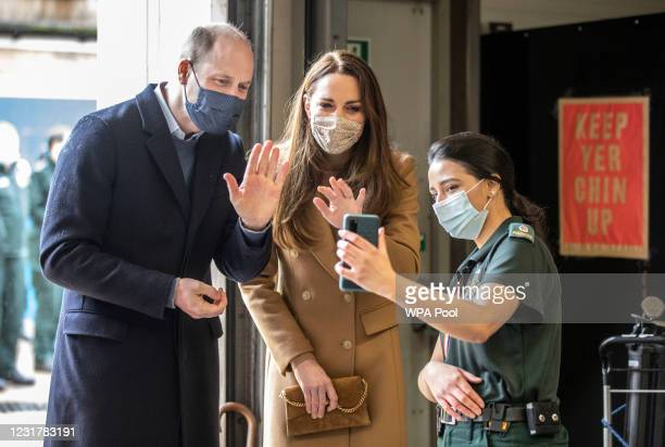 Prince William, Duke of Cambridge and Catherine, Duchess of Cambridge talk with the family of paramedic Jahrin Khan via a mobile phone during a visit...