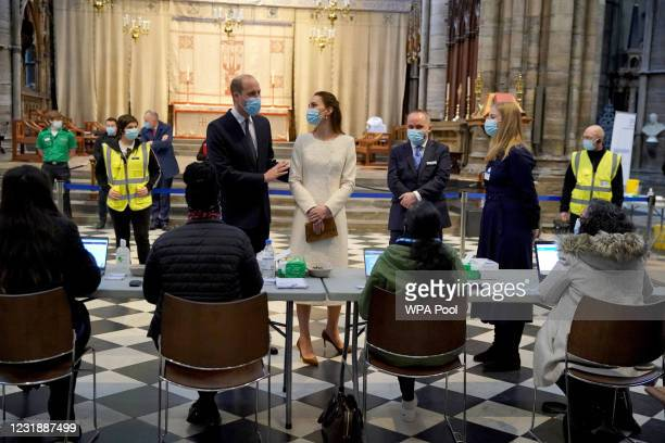 Prince William, Duke of Cambridge and Catherine, Duchess of Cambridge speak with staff during a visit to the Covid-19 vaccination centre at...