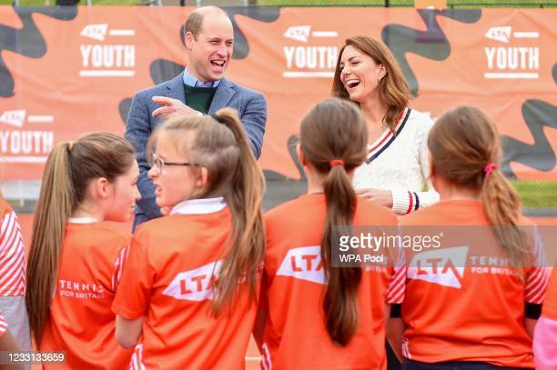 Prince William, Duke of Cambridge and Catherine, Duchess of Cambridge laugh as they speak to school children taking part in the Lawn Tennis...