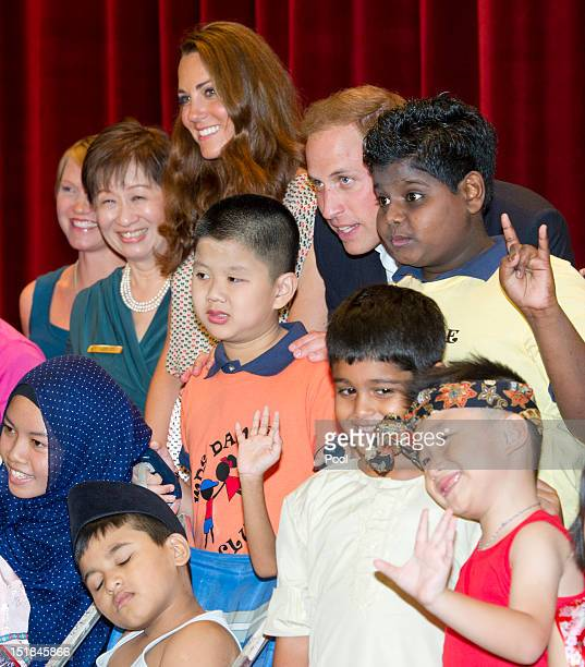 Prince William Duke of Cambridge and Catherine Duchess of Cambridge pose with children as they visit The Rainbow Centre on day 2 of the Diamond...