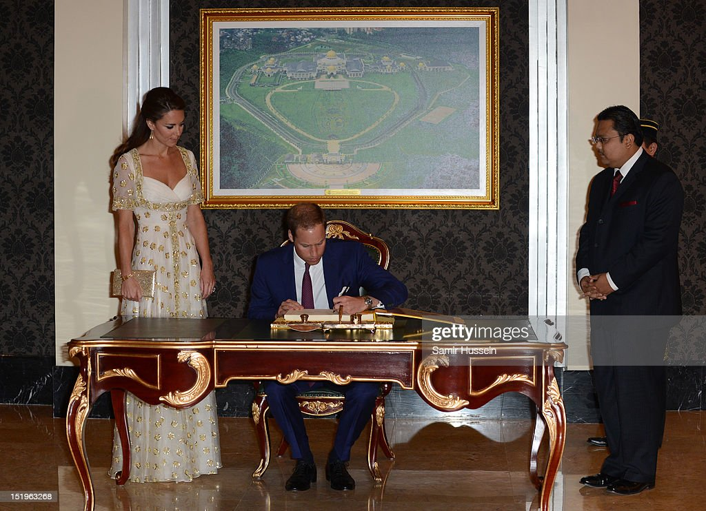Prince William, Duke of Cambridge (C) and Catherine, Duchess of Cambridge (L) sign the visitors' book during an official dinner hosted by Malaysia's Head of State Sultan Abdul Halim Mu'adzam Shah of Kedah on Day 3 of Prince William, Duke of Cambridge and Catherine, Duchess of Cambridge's Diamond Jubilee Tour of South East Asia at the Istana Negara on September 13, 2012 in Kuala Lumpur, Malaysia.
