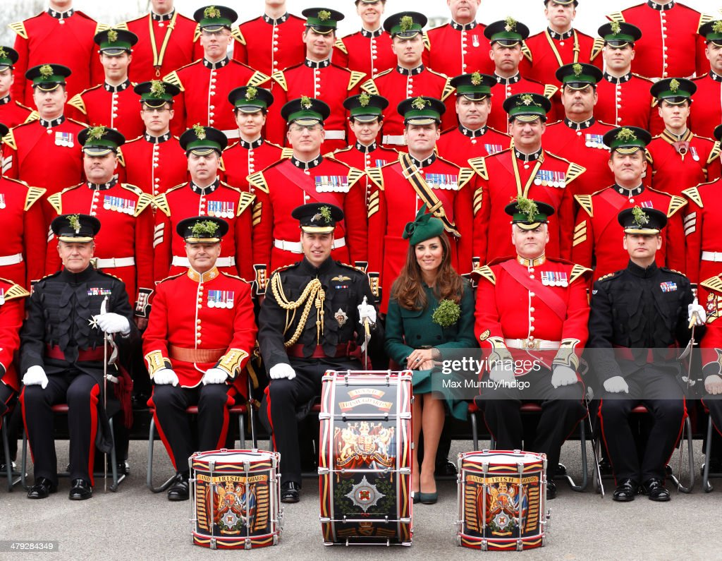 Prince William, Duke of Cambridge and Catherine, Duchess of Cambridge pose for a group photograph with soldiers of the Irish Guards as they attend the St Patrick's Day Parade at Mons Barracks on March 17, 2014 in Aldershot, England. Catherine, Duchess of Cambridge and Prince William, Duke of Cambridge visited the 1st Battalion Irish Guards to present the traditional sprigs of Shamrocks to the Officers and Guardsmen of the Regiment.