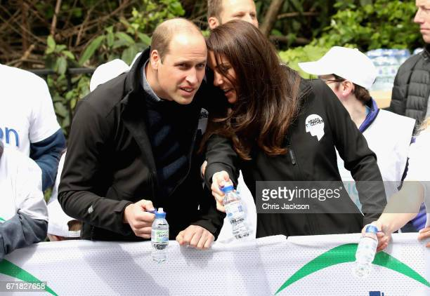 Prince William Duke of Cambridge and Catherine Duchess of Cambridge hand out water to runners during the 2017 Virgin Money London Marathon on April...