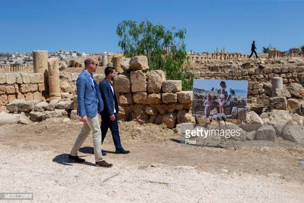 Prince William Duke of Cambridge and Crown Prince Hussein of Jordan walk past an enlarged photo of Catherine Duchess of Cambridge in her youth with...