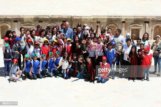 Prince William Duke of Cambridge and Crown Prince Hussein of Jordan pose for a group photo with children from the Makani Centre a free education and...