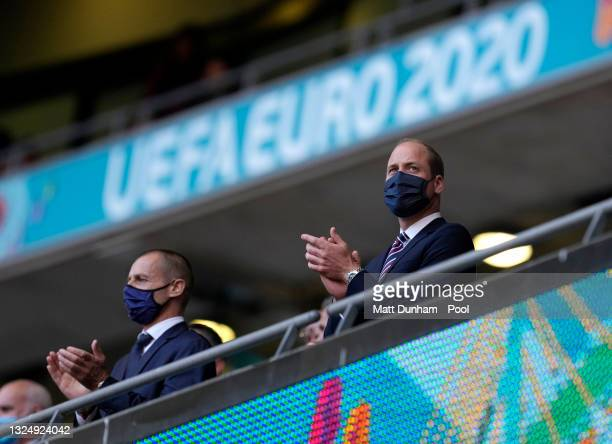 Prince William, Duke of Cambridge and President of The Football Association is seen wearing a face mask as he applauds from the stand alongside...