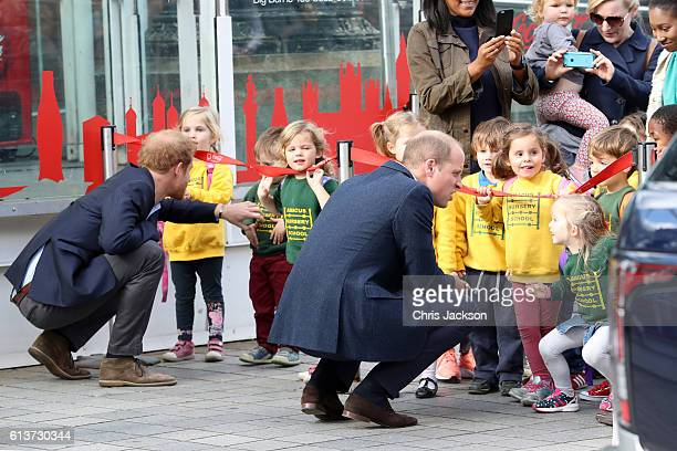 Prince William Duke of Cambridge and Prince Harry are greeted by children as they attend the World Mental Health Day celebration with Heads Together...