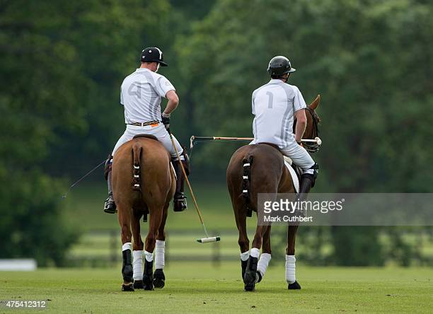 Prince William Duke of Cambridge and Prince Harry in action during day two of the Audi Polo Challenge at Coworth Park on May 31 2015 in London England