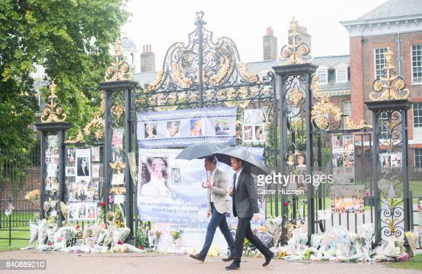 Prince William Duke of Cambridge and Prince Harry look upon flowers photos and other souvenirs left as a tribute to Princess Diana near The Sunken...