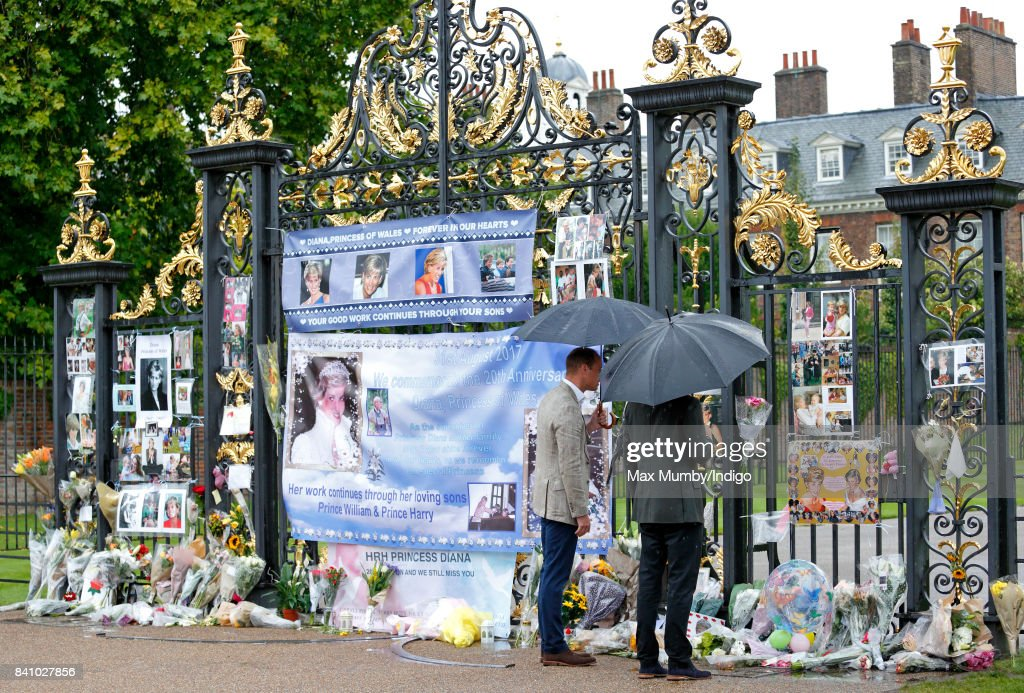Prince William, Duke of Cambridge and Prince Harry view tributes to Diana, Princess of Wales left at the gates of Kensington Palace after visiting the Sunken Garden on August 30, 2017 in London, England. The Sunken Garden has been transformed into a White Garden dedicated to Diana, Princess of Wales mother of The Duke of Cambridge and Prince Harry marking the 20th anniversary of her death.