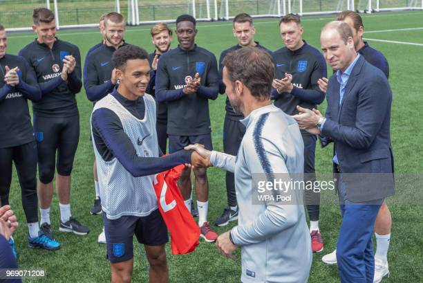Prince William Duke of Cambridge applauds as England player Trent Alexander Arnold shakes hands with England manager Gareth Southgate at the Facility...